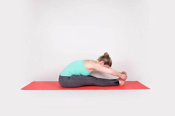 Ngồi gập người về phía trước giúp giảm mỡ bắp chân